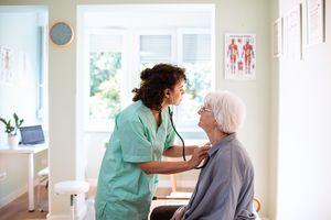 Nurse listening to patient lungs