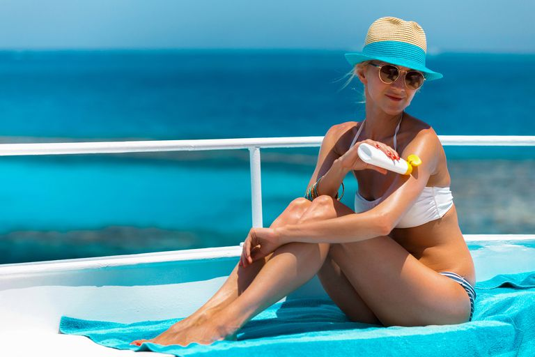 Young woman applying suntan lotion on a boat.