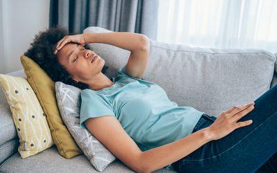 a sick woman lying on a sofa