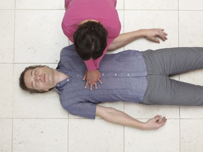 woman doing CPR on a man