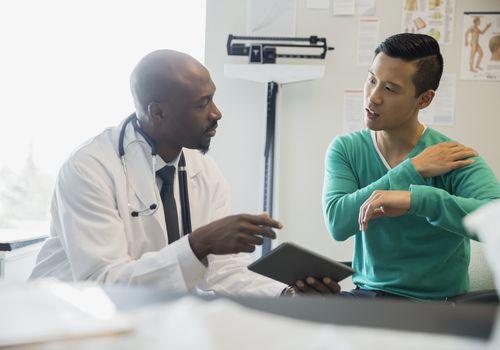 patient explaining shoulder pain to a doctor