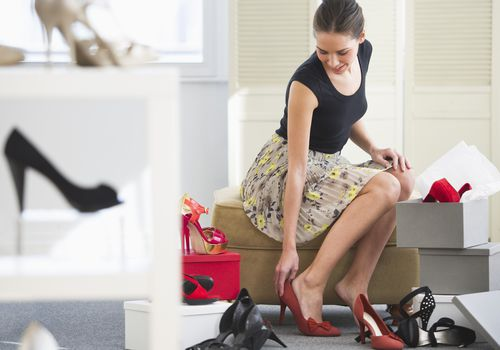 Woman trying on shoes, unaware that ill-fitted shoes can have serious consequences