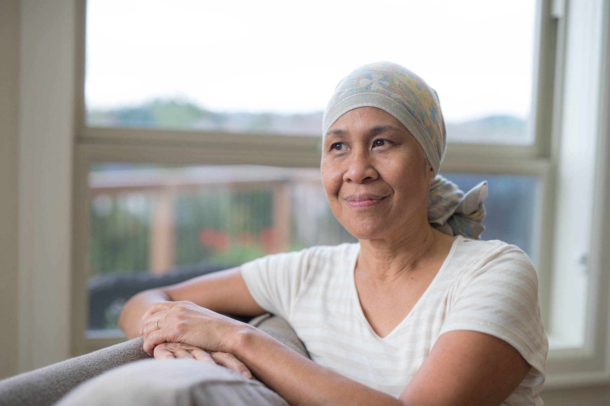 Woman sitting on a couch wearing a headwrap