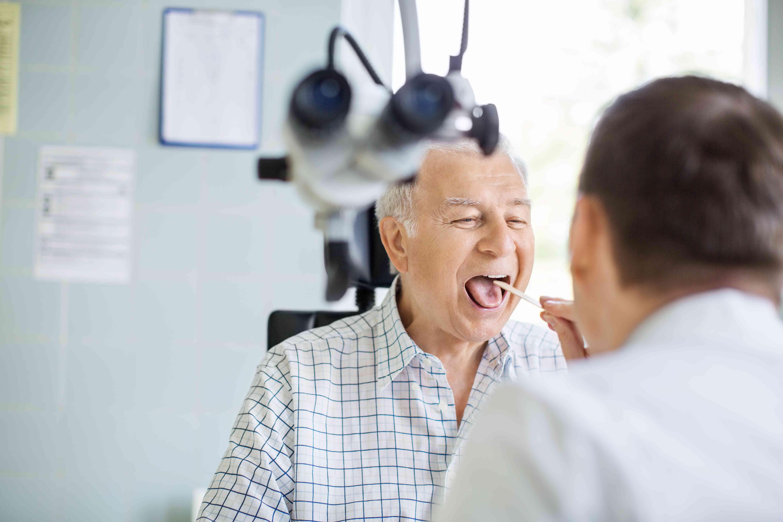 Doctor examining sore throat of senior patient