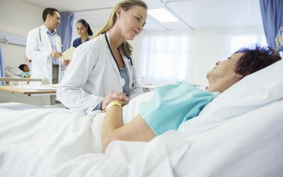 Woman hospitalized in observation status being checked on by her doctor.