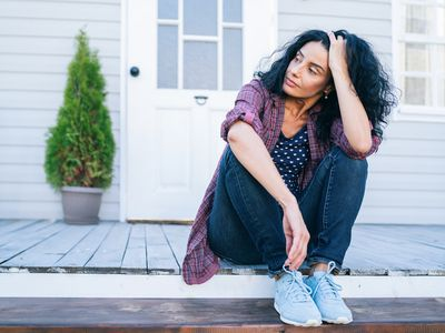 Person with brown skin and long, black hair sits on a porch stoop
