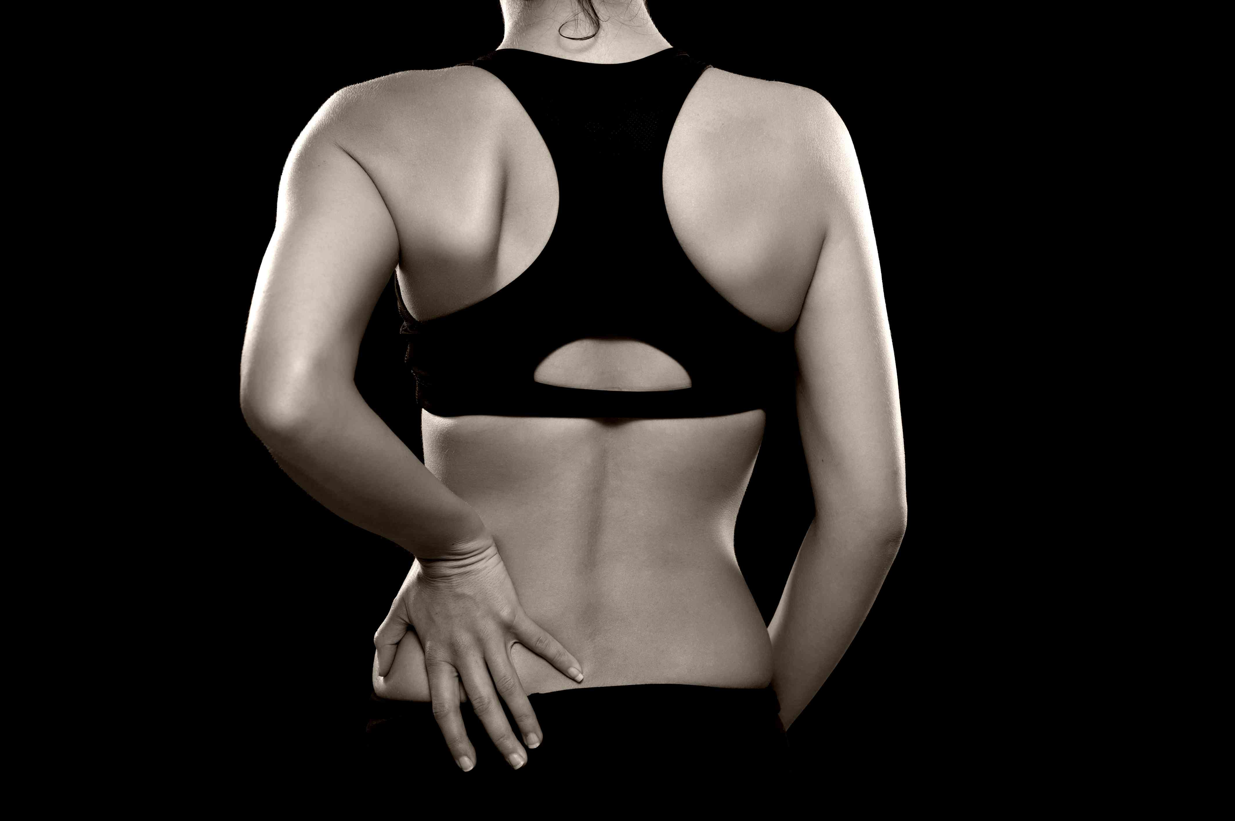A woman holding her low back in pain