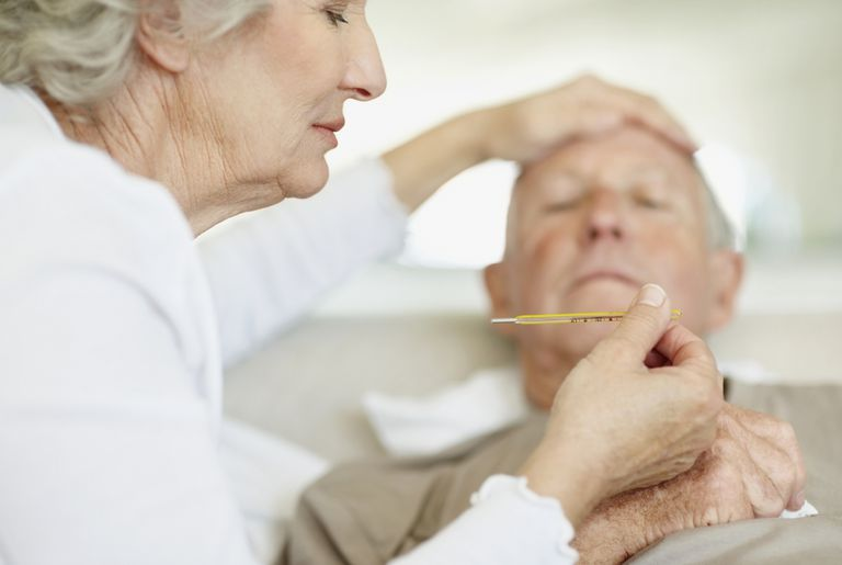 senior woman taking sick husband's temperature
