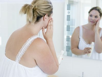 Woman Putting Lotion on Face in Bathroom