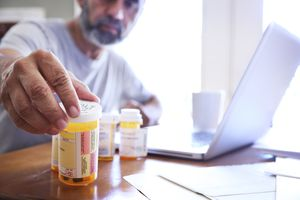 Hispanic Man Sitting At Dining Room Table Reaches For His Prescription Medications - stock photo