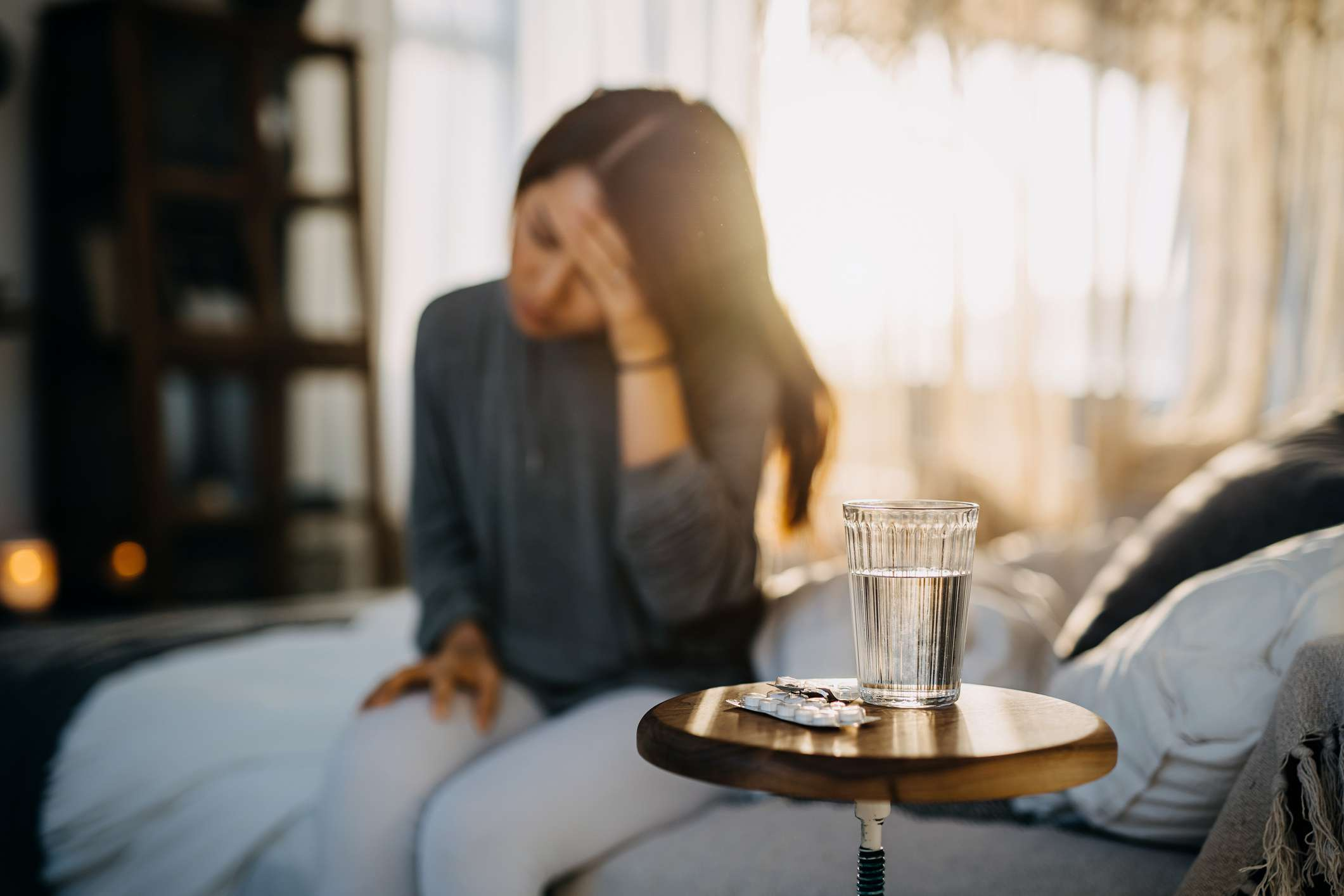 A young woman sits on the side of the bed, holding her head. A glass of water and medication sit on a table.