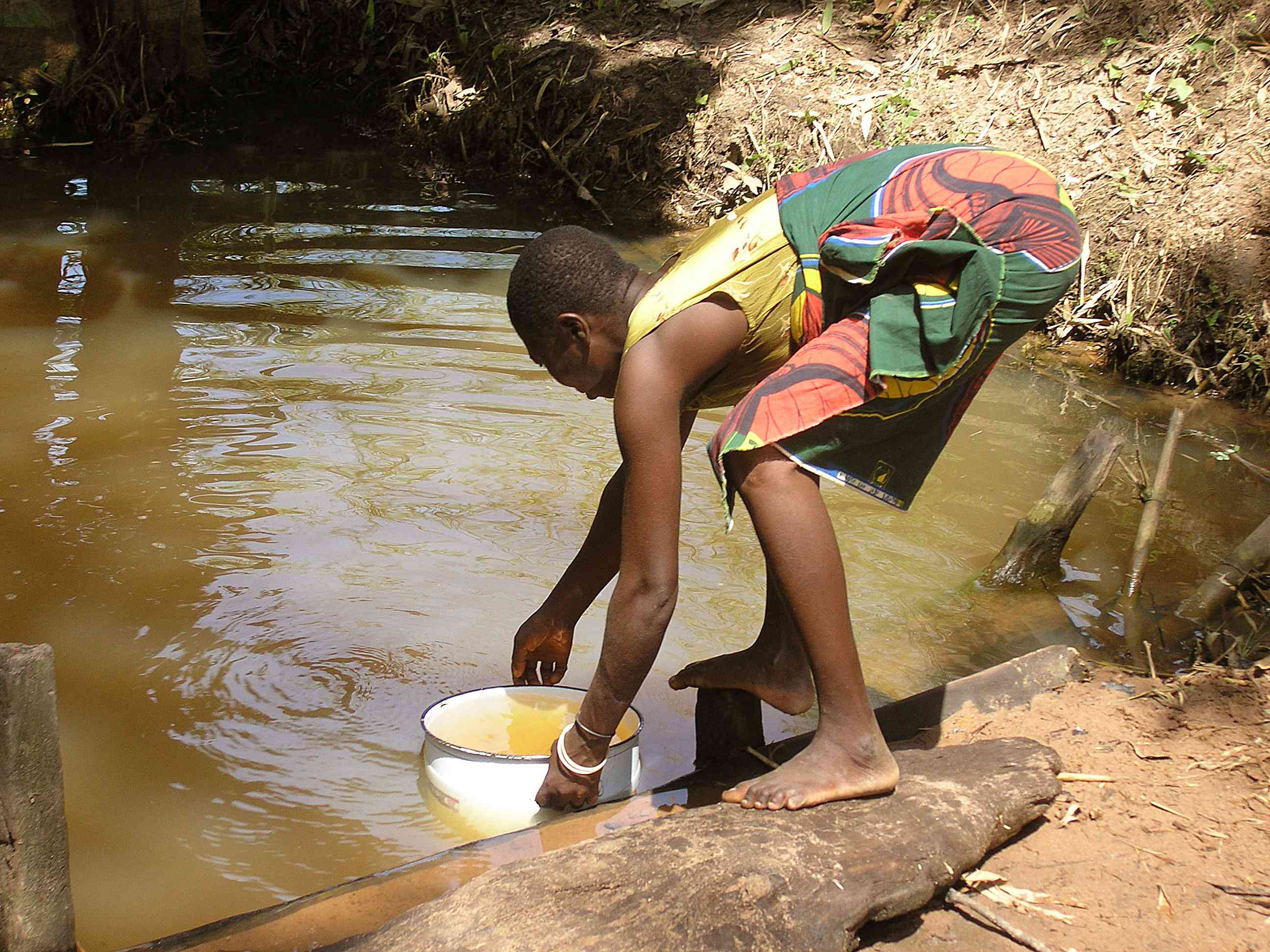 Young girl collecting water from a pond in Ogi, Nigeria
