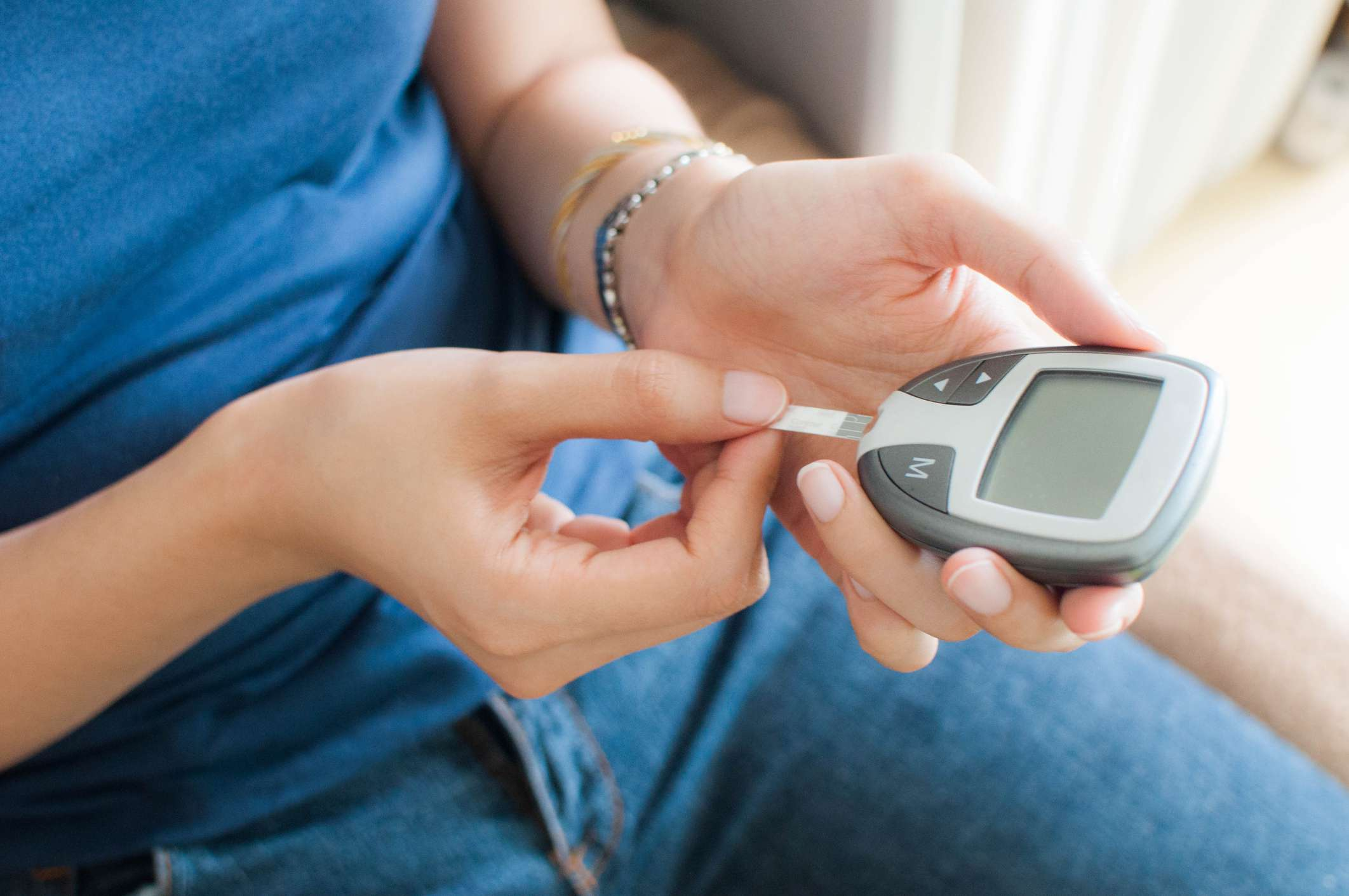 A young woman using a glucose meter