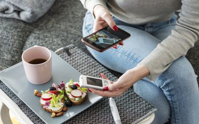 a woman taking a photo of her breakfast and blood sugar monitor