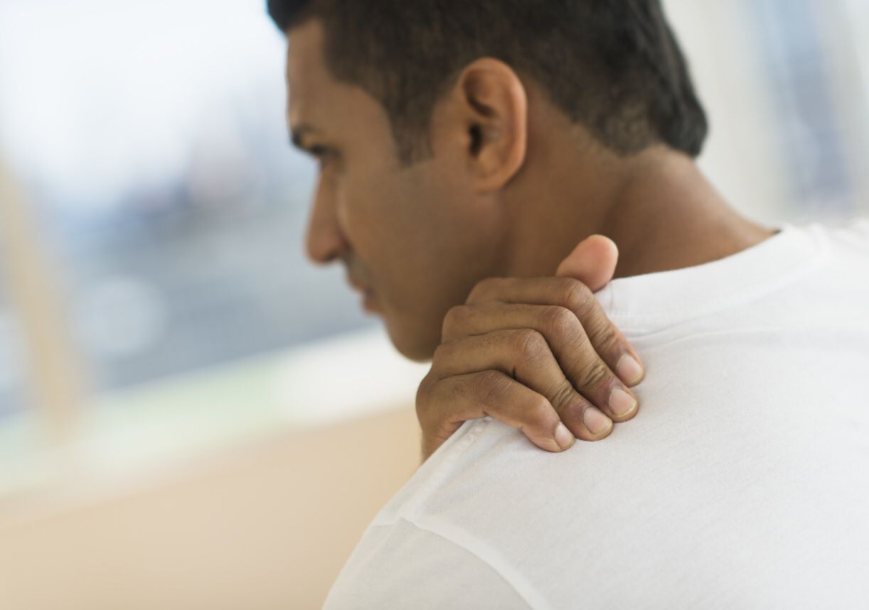 Photo of a man holding his painful neck.