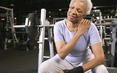 An elderly Black woman sits at a weight lifting machine, holding her shoulder with one hand, appearing to be in discomfort or pain.