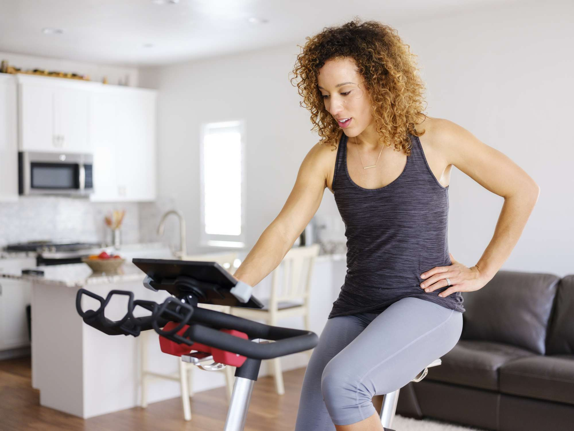 A woman on a stationary workout bike in her own home