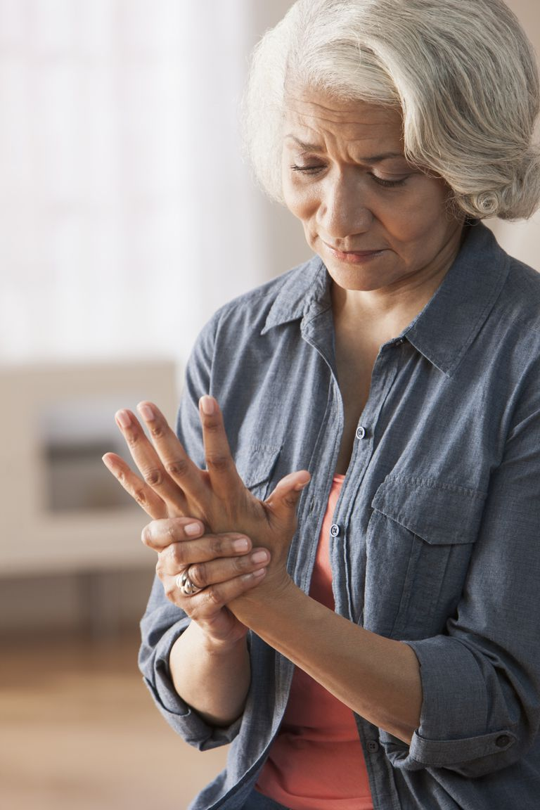 Older Black woman rubbing her hands
