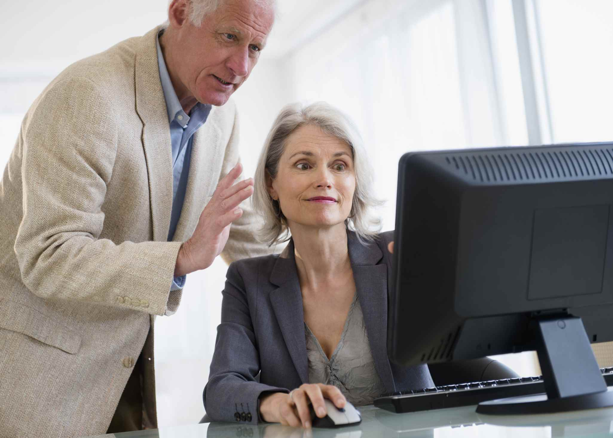 Male and female senior working together at computer