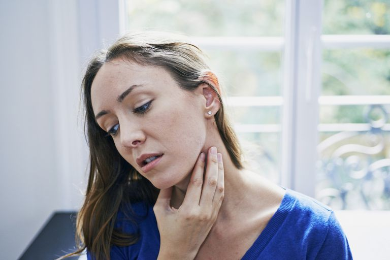 Woman feeling glands in throat