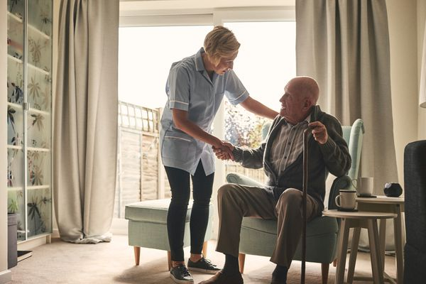 Nurse supporting senior patient at home