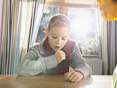 Boy coughing while sitting at a table