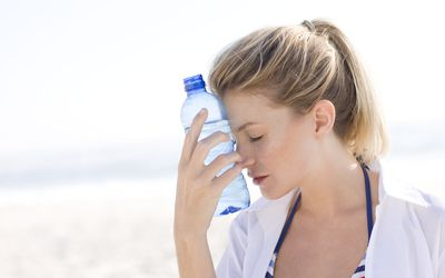 A woman holding a cold water bottle against her forehead
