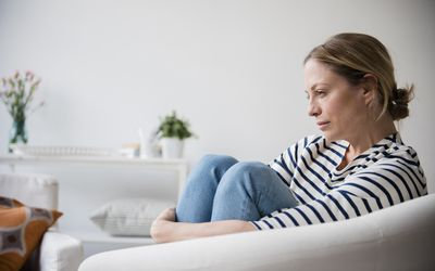 woman sitting in a chair, depressed