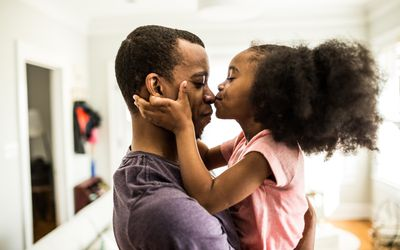 daughter kissing father on the nose - stock photo