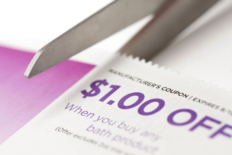 Scissors clipping a manufacturer's coupon