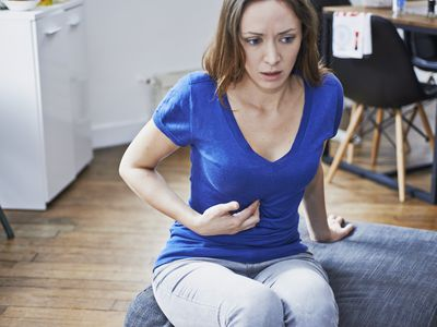 Woman experiencing heartburn.