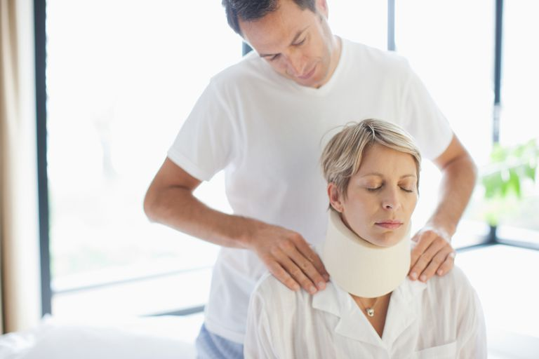 Woman wearing a neck brace getting her shoulders rubbed