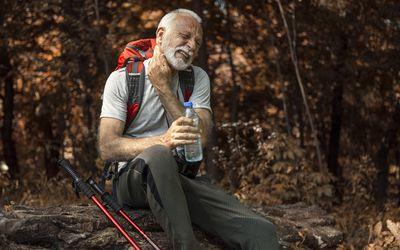 Elderly man sitting on a log in a forest holding a bottle of water with a hand on his neck