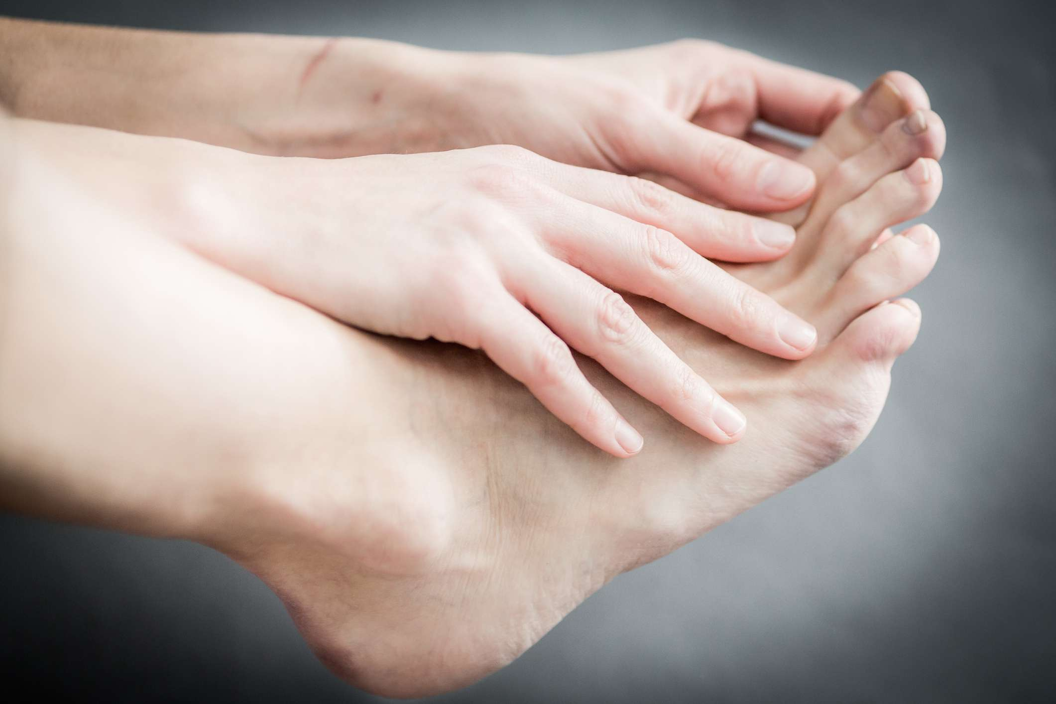 Close-up of person massaging their toe because of arthritis pain
