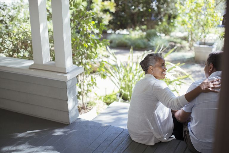 older woman having conversation with man on a porch