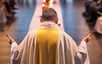 A priest from behind, leading a Catholic service or celebration.