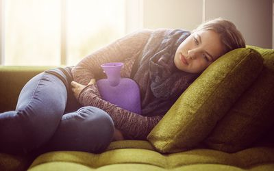 A woman laying on the couch in extreme mensural pain
