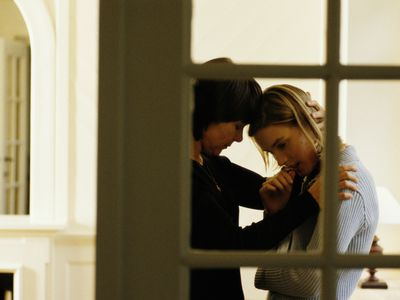 An older woman reassuring a distressed younger woman as seen through the windows of a door.