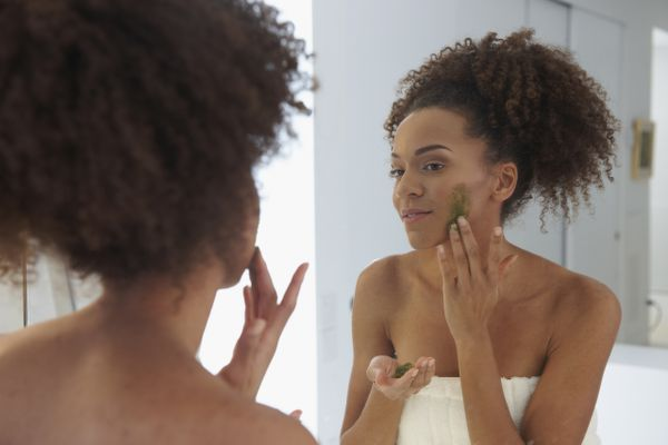 Mixed Race woman rubbing exfoliant on face at mirror