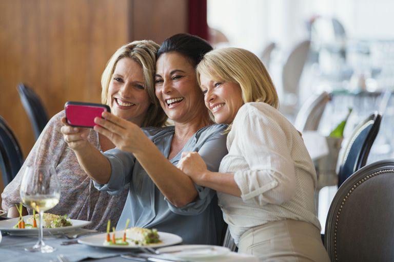 Three mature women taking selfie in restaurant
