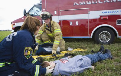 A group of Emergency Medical Technicians work on a patient in a field rescue.