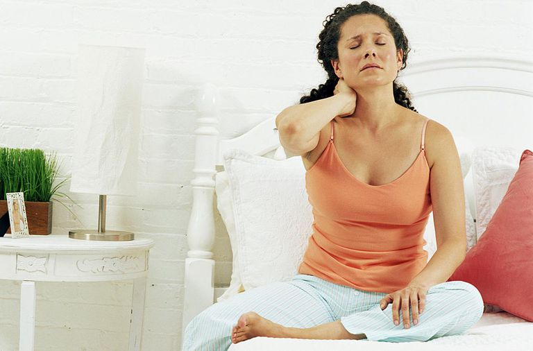 Woman sitting on bed rubbing neck, eyes closed