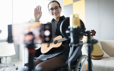 woman in a wheelchair on a video call learning guitar