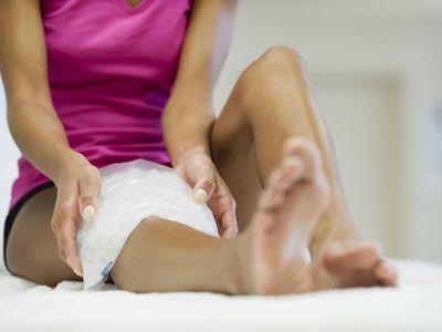 woman putting ice on sprained knee