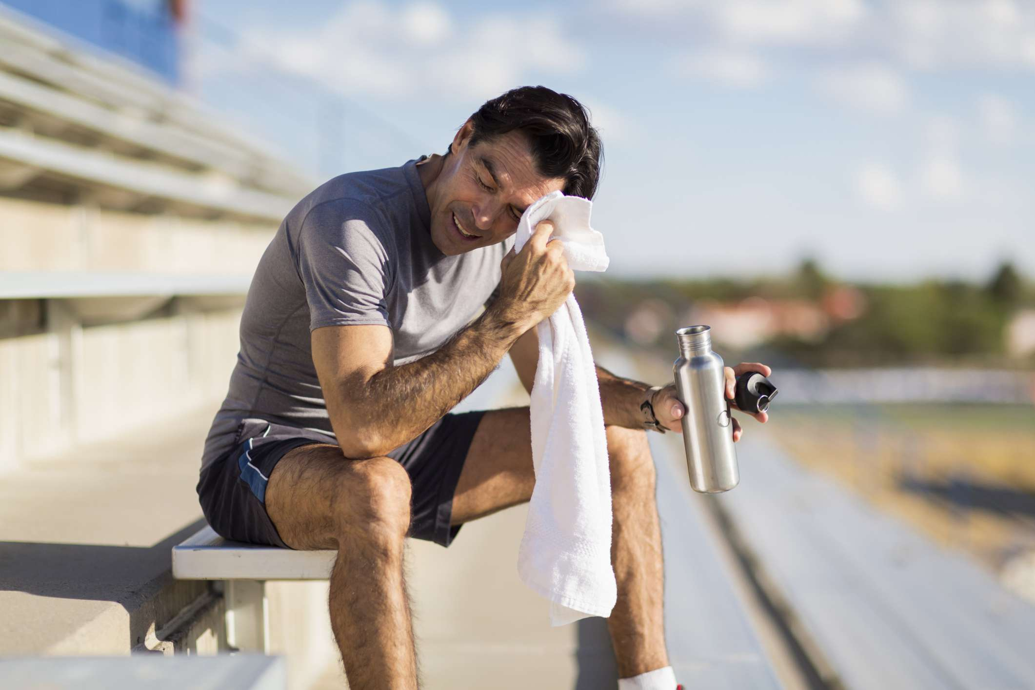 Man sitting on bleachers wiping his forehead with a towel