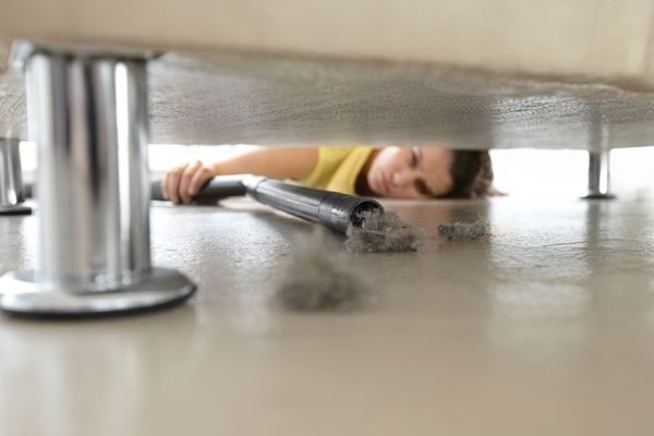 A woman vacuuming under her couch