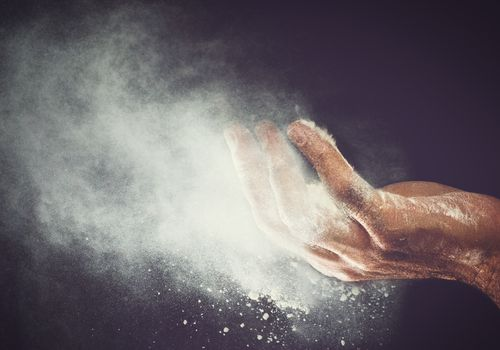 airborne wheat flour coming off person's hand