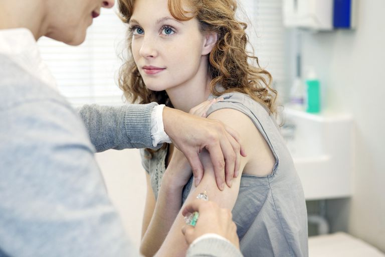 A woman receiving a shot from her doctor