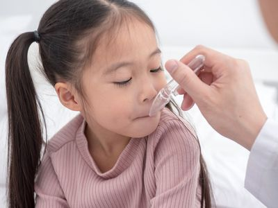 Small sick girl taking medicine - stock photo