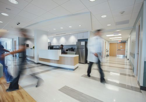 Doctor sitting at reception while hospital staff working